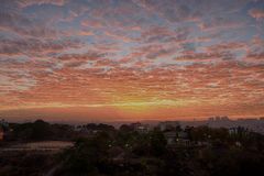 Hide and seek of sunrise. Bangalore , India - February 28 , 2018 : Beautiful cloud formation and hide and seek of sunrise within these clouds in South Bangalore Stock Photos