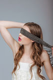 Hide and Seek. Woman Holding a Strap on her Face. Puzzle Stock Image