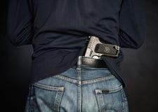 Hided handgun under the denim belt. Stock Photos