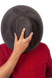Hiding. A man covers his head with a cowboy hat - in hiding Royalty Free Stock Images
