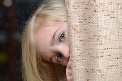 Hiding. Child hiding behind a curtain Stock Photo