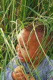 Hiding. A young boy is hiding amongst the tall grass in a field Stock Photo