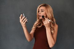 Hiding all imperfections. Attractive young woman in dress looking in mirror and applying make-up brush while standing against grey background Royalty Free Stock Images