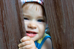 Hiding baby. One year old baby playing hide-and-seek Royalty Free Stock Image