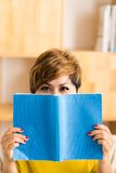 Hiding behind a book Royalty Free Stock Image