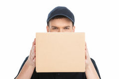 Hiding behind the box. Portrait of confident young deliveryman l Royalty Free Stock Photos