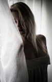 Hiding behind the curtain. Blond woman hiding behind the curtain royalty free stock images
