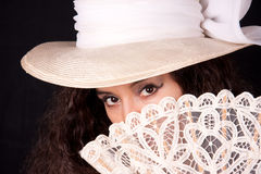 Hiding behind the fan. Woman with hat hiding her face behind her lace fan Royalty Free Stock Photos