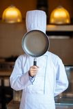 Hiding behind frying pan Stock Photography