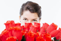 Hiding behind red roses. Woman hiding her face behind red roses - isolated on white Royalty Free Stock Images