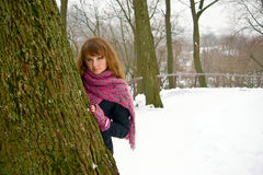 Hiding Behind the Tree. Portrait of a young woman with pink scarf and gloves, she is hiding behind the tree Royalty Free Stock Photos
