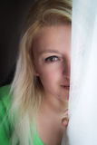 Hiding. Blond woman hiding behind white curtain Stock Photos
