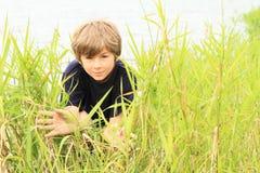 Hiding boy. Kid - boy hiding in the reeds by lake Stock Photos