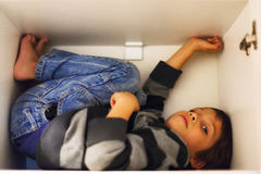 Hiding child. Child hiding in a closet or box Stock Photography
