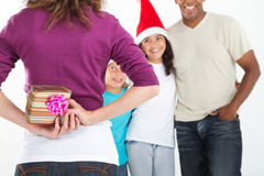 Hiding christmas gift. Young mother hiding Christmas gift behind her back to surprise her family Stock Images