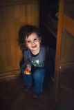 Hiding in the closet. Playful caucasian girl hiding in the closet, making funny face. High iso noise visible stock images