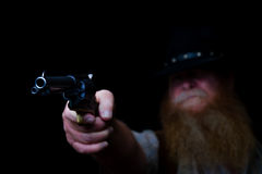 Hiding in the darkness before he shoots. Image shows an older cowboy holding his pistol up in the middle of the night hiding about ready to shoot Royalty Free Stock Photos