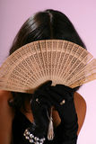 Hiding face. Young woman hiding face behind a fan Stock Images