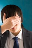 Hiding face. Portrait of young businessman hiding his face by hand Royalty Free Stock Images