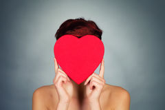 Hiding face behind red heart Stock Image