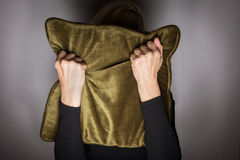 Hiding in Fear. Mentally ill woman hiding in fear behind pillow Royalty Free Stock Image