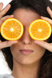 Hiding her eyes with oranges Royalty Free Stock Images