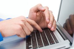 Hiding information. Close-up of male hand over laptop keyboard while the other one hiding forefinger Royalty Free Stock Photo