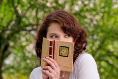 Hiding and lurking. Cute and funny caucasian brunette giel in spring forest hiding behind book -shot on location with flash Royalty Free Stock Photos