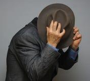 Hiding man. A man hiding behind his hat stock photos