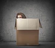 Hiding Man. Man hiding behind a box Royalty Free Stock Images