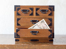 Hiding money in an antque miniture drawer called Tansu Yokin in Stock Image