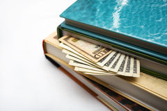 Hiding money in books. Closeup of money sticking out of the pages of a stack of books Stock Photography