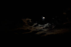 The Hiding Moon. The moon, hiding behind a large cloud Stock Images
