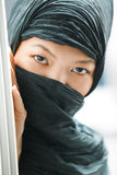 Hiding. Oriental lady in black hijab hiding Stock Photography