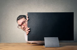 Hiding place. Man in desktop hiding behind the screen of the computer Stock Photography