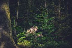 Hiding Poacher in Deep Forest Stock Photo