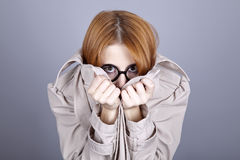 Hiding red-haired girl in glasses and cloak. Stock Photos