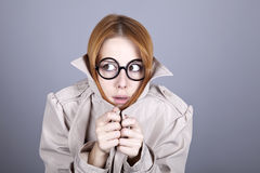 Hiding red-haired girl in glasses and cloak. Stock Images