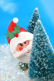 Hiding Santa Claus. Winter scene in glitter, Santa Claus is playing hide and go seek, peeking or hiding  behind miniature pine trees Royalty Free Stock Photos
