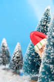 Hiding Santa Claus. Winter scene in glitter, Santa Claus is playing hide and go seek, peeking or hiding  behind miniature pine trees Stock Photography