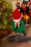 Hiding in a santa hat. Funny little girl hiding in a santa claus hat Royalty Free Stock Photos