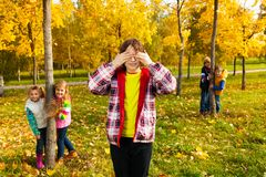 Hiding and seeking. Group of five kids play hide and seek with boy counting and friends hiding behind the trees standing in autumn park Stock Photography