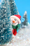 Hiding Snowman. Winter scene in glitter, a snowman  is playing hide and go seek, peeking or hiding  behind miniature pine trees Royalty Free Stock Images