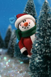 Hiding Snowman. Winter scene in glitter, a snowman  is playing hide and go seek, peeking or hiding  behind miniature pine trees in the night Royalty Free Stock Image