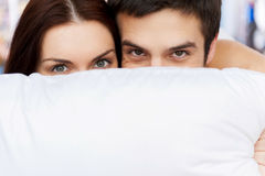 Hiding their faces behind the pillow. Cheerful young loving couple lying in bed and looking out of the pillow Royalty Free Stock Image