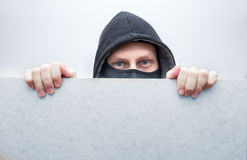 Hiding thief. Thief in mask hiding behind wall Royalty Free Stock Photography