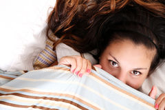 Hiding under a blanket. A young woman hiding under a blanket Stock Photography