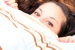 Hiding under a blanket. A young woman hiding under a blanket Stock Image