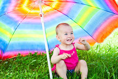 Hiding under a colorful umbrella Stock Photo