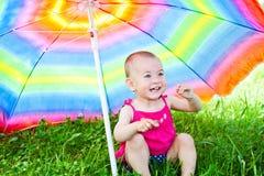 Hiding under a colorful umbrella stock photo